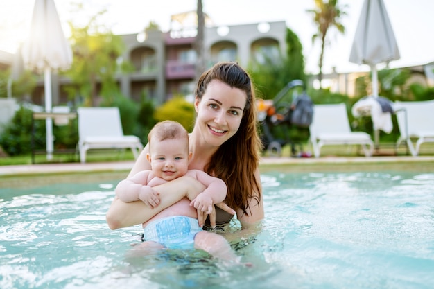 Belle mère caucasienne debout dans la piscine et tenant son fils de 6 mois. bébé regardant la caméra et souriant.