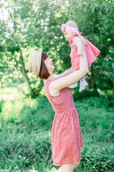 Belle mère avec le chapeau de paille et sa petite fille en plein air, la famille regarde dans une robe rose. look familial. jeune maman jette bébé dans le ciel, aux beaux jours.