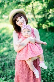 Belle mère avec le chapeau de paille et sa petite fille en plein air, la famille regarde dans une robe rose. portrait en plein air de famille heureuse. look familial. émotions humaines positives, sentiments, émotions.