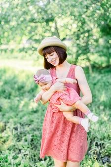Belle mère avec le chapeau de paille et sa petite fille en plein air, la famille regarde dans une robe rose. portrait en plein air de famille heureuse. look familial. heureuse mère s'amusant avec sa fille