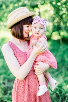 Belle mère avec le chapeau de paille et sa petite fille en plein air, la famille regarde dans une robe rose. portrait en plein air de famille heureuse. look familial. maman embrasse sa fille dans une joue.