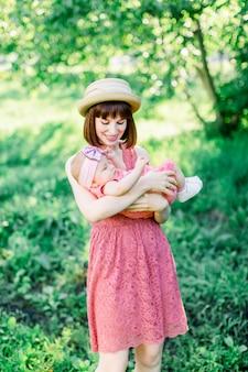 Belle mère avec le chapeau de paille et sa petite fille en plein air, la famille regarde dans une robe rose. portrait en plein air de famille heureuse. look familial. mère bébé, dans parc, portrait