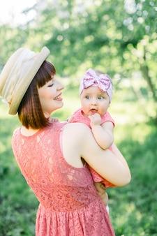 Belle mère avec le chapeau de paille et sa petite fille en plein air, la famille regarde dans une robe rose. portrait en plein air de famille heureuse. look familial. mère et sa fille dans le parc d'été.