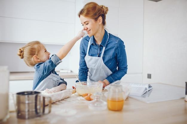 Belle mère dans une chemise bleue et un tablier prépare le dîner à la maison dans la cuisine