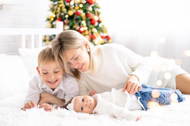 Belle mère avec deux enfants célèbrent noël à la maison vacances du nouvel an noël tre