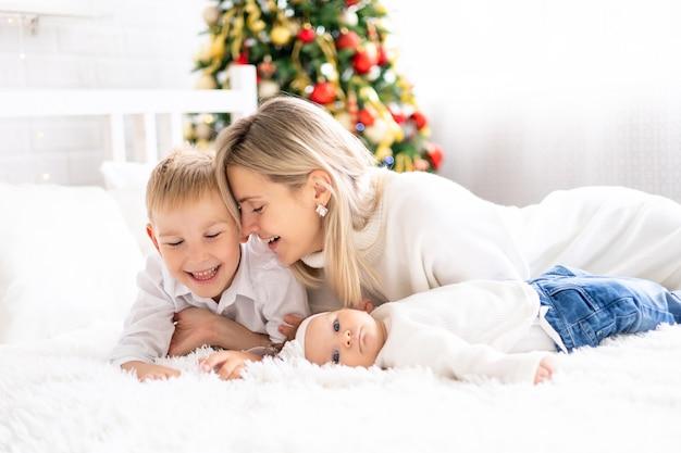 Belle mère avec deux enfants fête noël à la maison vacances du nouvel an arbre de noël