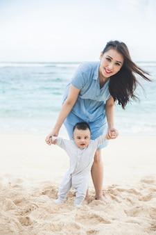 Belle mère enseigne à son fils se promène sur la plage