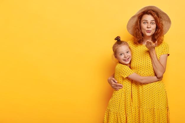 Belle mère et fille rousse posant dans des robes similaires