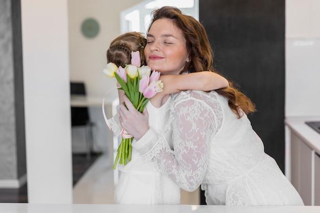 Belle mère et fille s'embrassant à la fête des mères avec des fleurs de tulipes