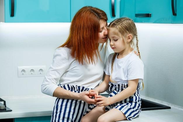 Belle mère et fille s'embrassent et sourient joyeusement, assises dans la cuisine. concept de famille, d'enfants, de maternité et de cuisine. relations familiales heureuses