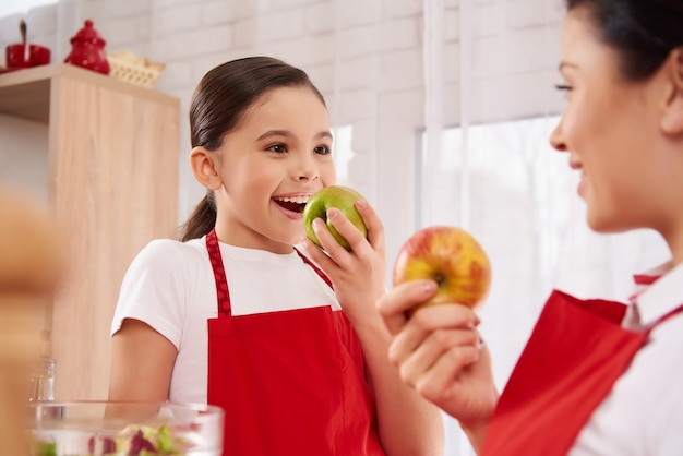 Belle mère et fille en tabliers mangent des pommes