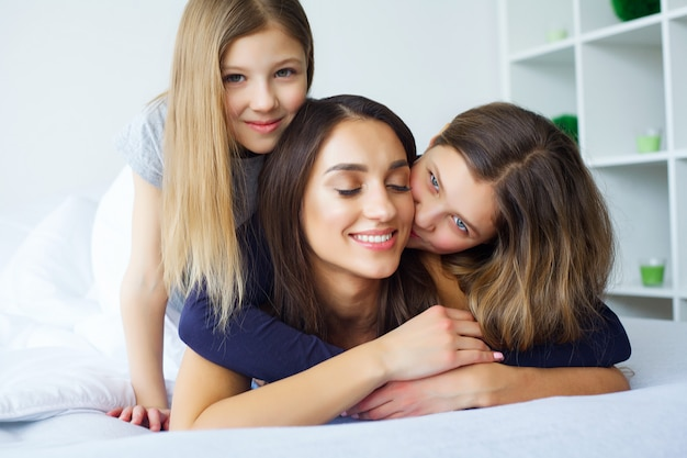 Belle mère et filles étreignent, regardant et souriant assis sur lit à la maison