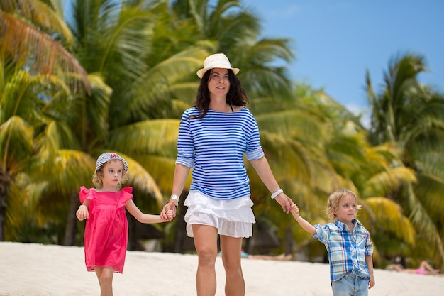 Belle mère fils et fille marchant sur la plage de l'océan indien