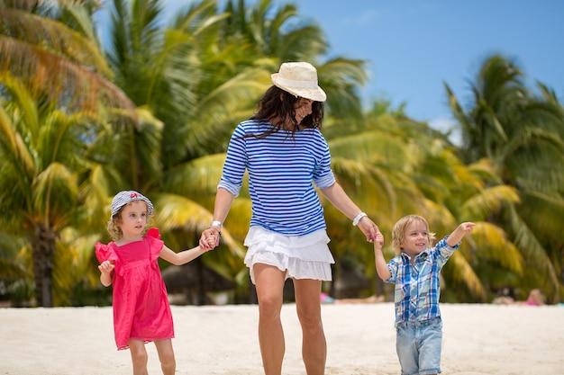 Belle mère, fils et fille marchant sur la plage de l'océan indien.