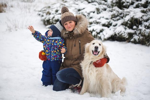 Belle mère et fils jouant avec mon chien dans la neige. golden retriever