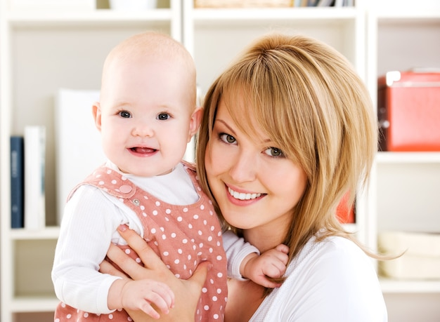 Belle mère heureuse tenant bébé nouveau-né sur les mains - à l'intérieur