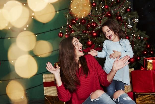 Belle mère jouant avec sa fille dans la magnifique chambre décorée avec arbre de noël