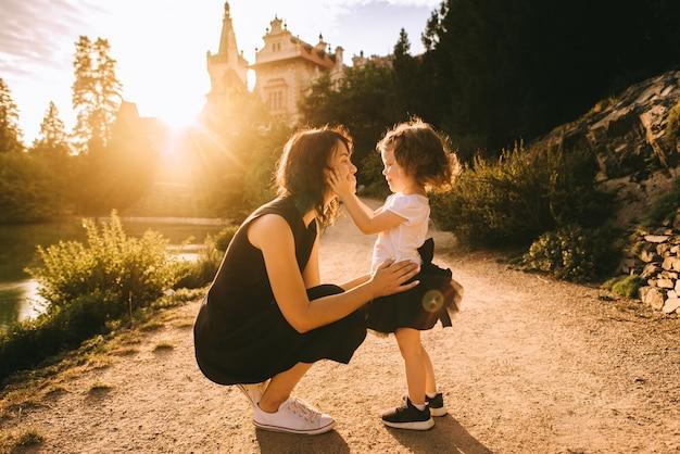 Une belle mère jouant avec sa jolie fille dans le parc d'été ensoleillé près du château au coucher du soleil