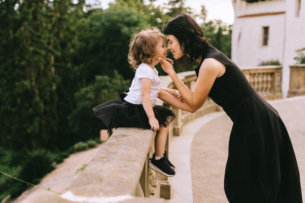 Une belle mère jouant avec sa jolie fille dans le parc d'été ensoleillé près du château