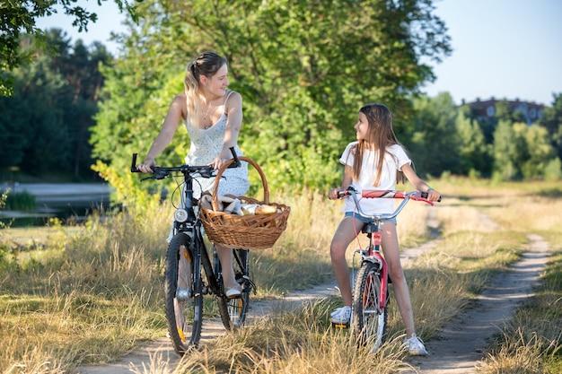 Belle mère joyeuse allant pique-niquer avec sa fille à vélo