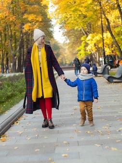 Belle mère marchant avec son fils sur le parc d'automne