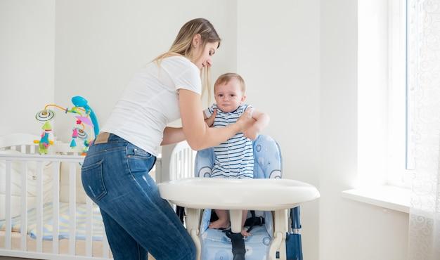Belle mère nourrissant son petit garçon dans une chaise haute avec de la bouillie