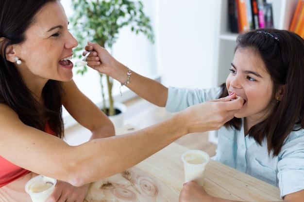 Belle mère et sa fille qui mangent de l'iogur à la maison.