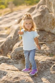 Belle mère et sa jolie fille aux cheveux longs marchent sur un pré de pierre