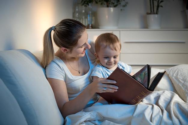 Belle mère souriante lisant une histoire à son petit garçon avant d'aller dormir