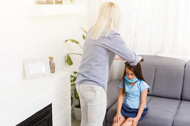 Belle mère tressant les cheveux de sa fille dans la cuisine. jolie petite fille aux cheveux longs. intérieur de maison confortable. famille heureuse et en bonne santé.