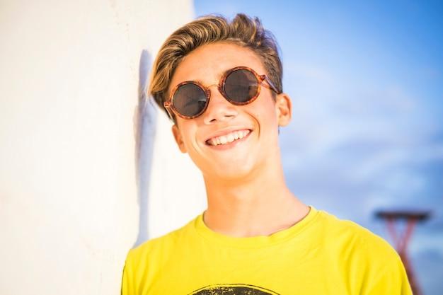 Belle et merveilleuse belle jeune mannequin de 14 ans pose et sourit à la caméra sous la lumière du soleil. concept de vacances et de bonheur avec garçon blond