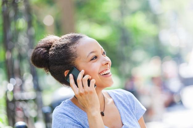 Belle métisse jeune femme parlant au téléphone mobile