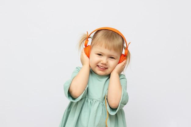 Belle mignonne petite fille heureuse avec des écouteurs sur fond blanc