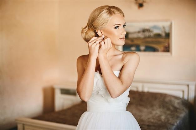 Belle et à la mode jeune mariée, fille blonde modèle sexy aux yeux bleus et coiffure élégante en robe blanche ajustant sa boucle d'oreille et posant à l'intérieur, préparation du mariage le matin