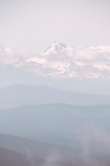 Belle montagne couverte de neige et entourée de nuages pendant un temps brumeux