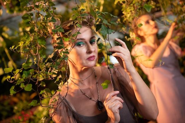 Belle nature. belle jolie femme vous regarde tout en touchant une branche d'arbre