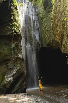 Belle nature. gentille fille brune levant les bras tout en profitant des sons de l'eau, debout dans la gorge