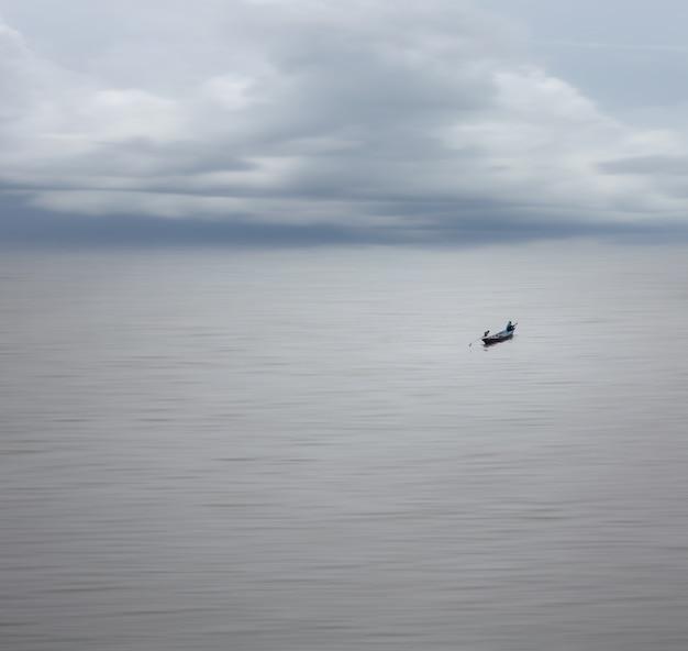 Belle nature avec une longue distance de pêcheur sur le bateau dans une mer douce et un ciel clair, effet de flou de mouvement et minimalisme.