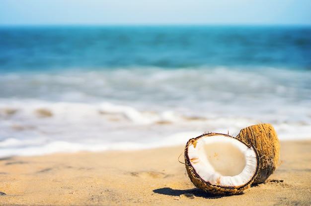 Belle noix de coco mûre le lac divisé en 2 moitiés se trouve sur une plage de sable blanc