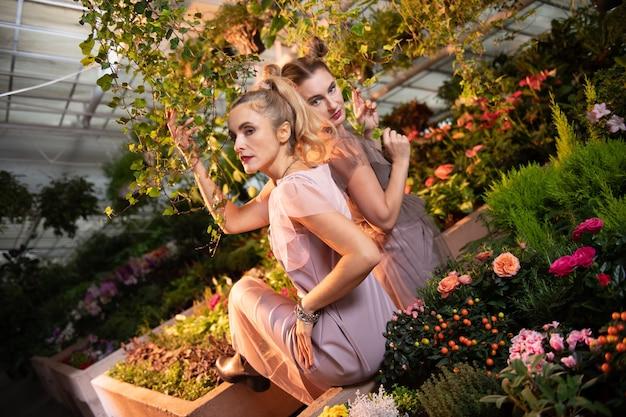 Belle orangerie. jolies femmes attirantes touchant des plantes tout en visitant un jardin botanique