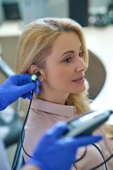 Belle patiente caucasienne pensive, assise immobile pendant un test d'audiométrie effectué par un professionnel de la santé