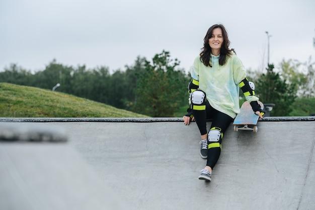 Belle patineuse souriante reposant sur un pont. elle porte un équipement de protection. vue frontale. nature en arrière-plan.