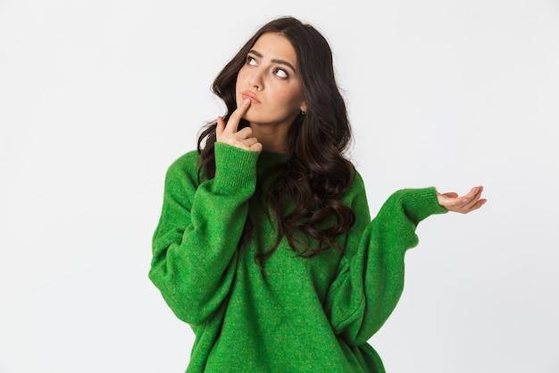 Belle pensée jeune femme habillée en pull vert posant isolé sur un mur blanc.