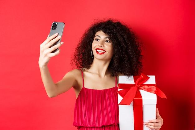 Belle petite amie aux cheveux bouclés, vêtue d'une robe de soirée, prenant selfie avec un cadeau d'amant, photographiant sur smartphone et souriant, debout sur fond rouge.