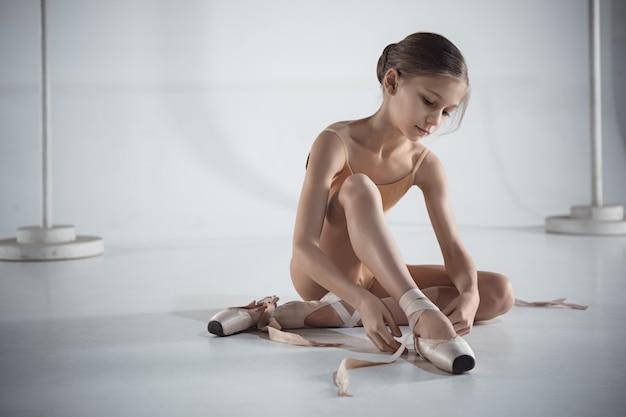 Belle petite ballerine mettant des chaussons de pointe
