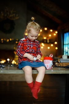 Une belle petite blonde dans une chemise à carreaux traditionnelle ouvre une barre de chocolat de son doux cadeau de noël
