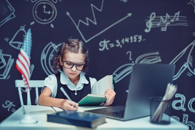 Belle petite écolière assise au bureau et étudie en ligne avec un ordinateur portable sur fond noir avec...