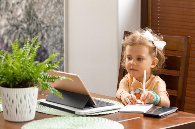 Belle petite fille de 3 ans aux cheveux bouclés est assise à table et étudie en ligne avec tablette à la maison. concept d'éducation de la petite enfance.
