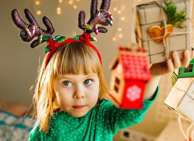 Belle petite fille de 3 ans tenant une boîte-cadeau décorée de forme de coeur de tranche d'agrumes séchés. mise au point sélective.