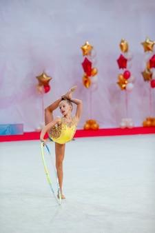 Belle petite fille active de gymnaste avec sa performance sur le tapis